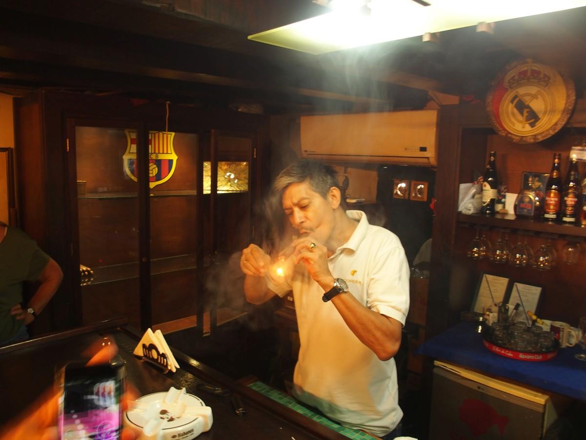 Ein Mann zündet sich eine Zigarre an.